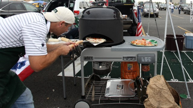 EAST RUTHERFORD, NJ - SEPTEMBER 11:  New York Jets fans Andrew Brucker of Mendham, NJ prepares a pizza as he tailgates outside the stadium prior to the Jets playing against the Dallas Cowboys during their NFL season opening game during their NFL Season Opening Game at MetLife Stadium on September 11, 2011 in East Rutherford, New Jersey.  A Pat Tillman jersey is seen hanging from Brucker's tailgate tent. (Photo by Elsa/Getty Images)
