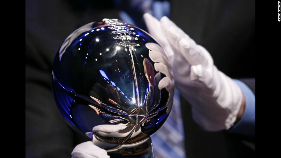 A man sets up the Lombardi Trophy for display before the head coaches' news conference.