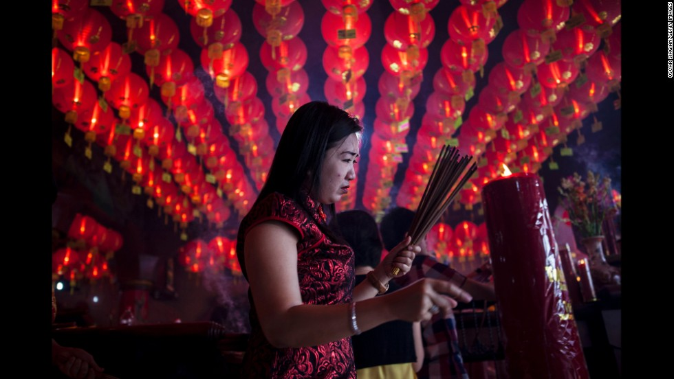 A woman holds incense sticks as she attends prayers at Bun San Bio Temple in Tangerang, Indonesia, on January 31.
