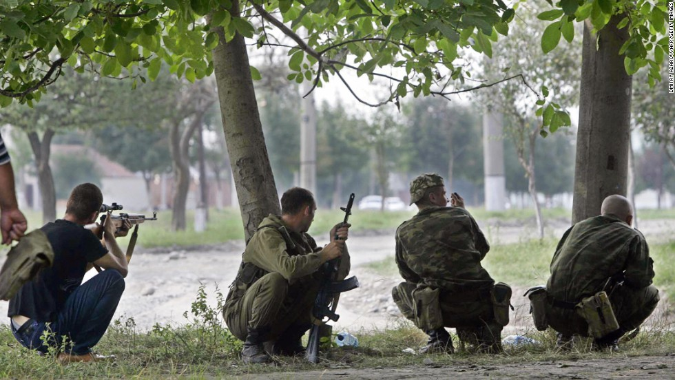 Ossetian soldiers take position near the school where a group of gunmen, wearing belts laden with explosives, held the hostages.