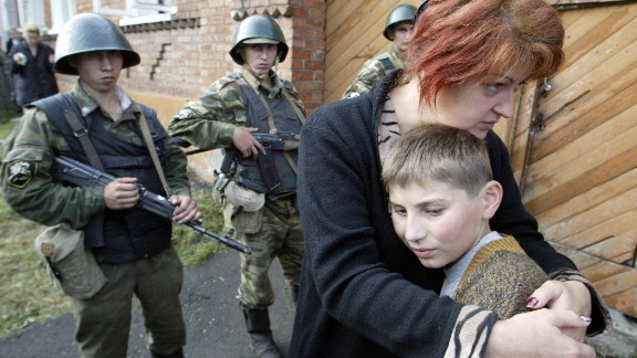 A mother hugs her son in front of soldiers cordoning off the school building.