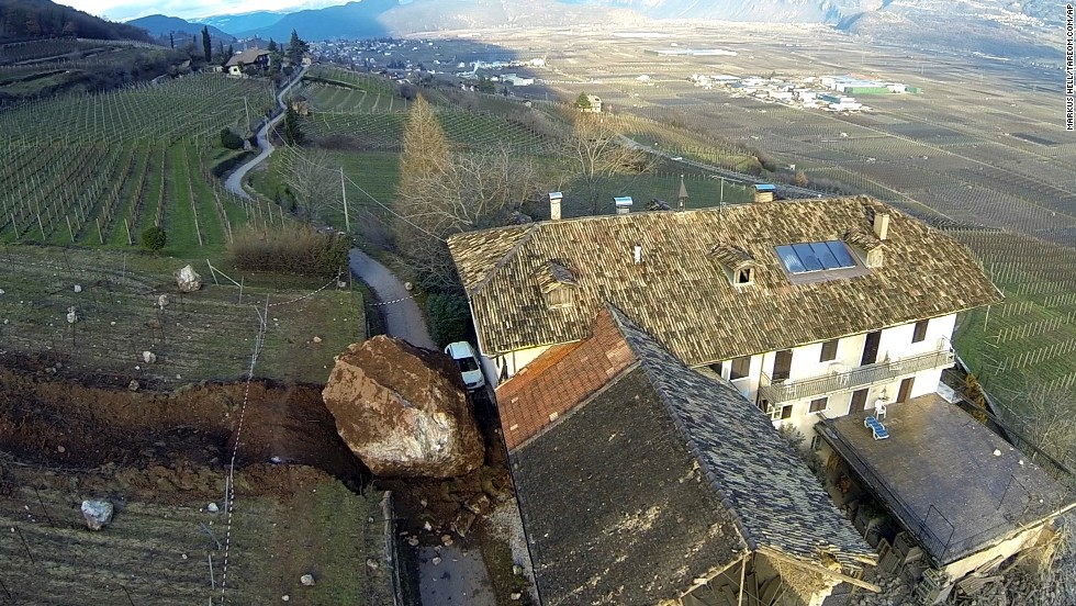 A boulder sits next to a farmhouse in northern Italy on January 23, two days after a landslide sent several large rocks tumbling downhill. The adjacent barn wasn't as lucky.