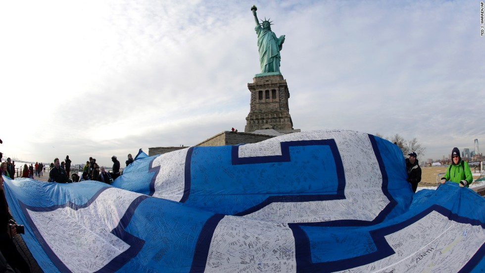 "A giant Seahawks ""12th Man"" flag that flew on the Space Needle in Seattle before being signed by fans and brought to New York, is displayed at the Statue of Liberty on January 31. Sunday's game will be held in East Rutherford, New Jersey, just outside of New York City."
