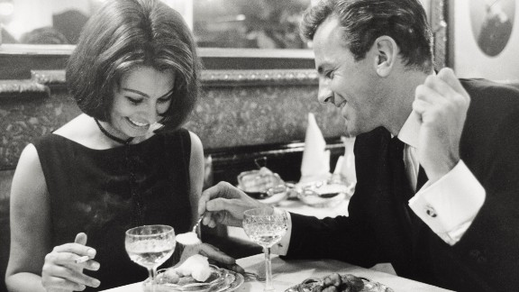 """Loren has dinner with Schell at a restaurant in Hamburg, Germany, during the filming of """"The Condemned of Altona"""" in 1962."""