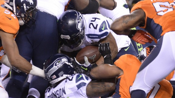 Marshawn Lynch (no 24) forces his way through a pack of players to score the opening touchdown of the game for the Seahawks.