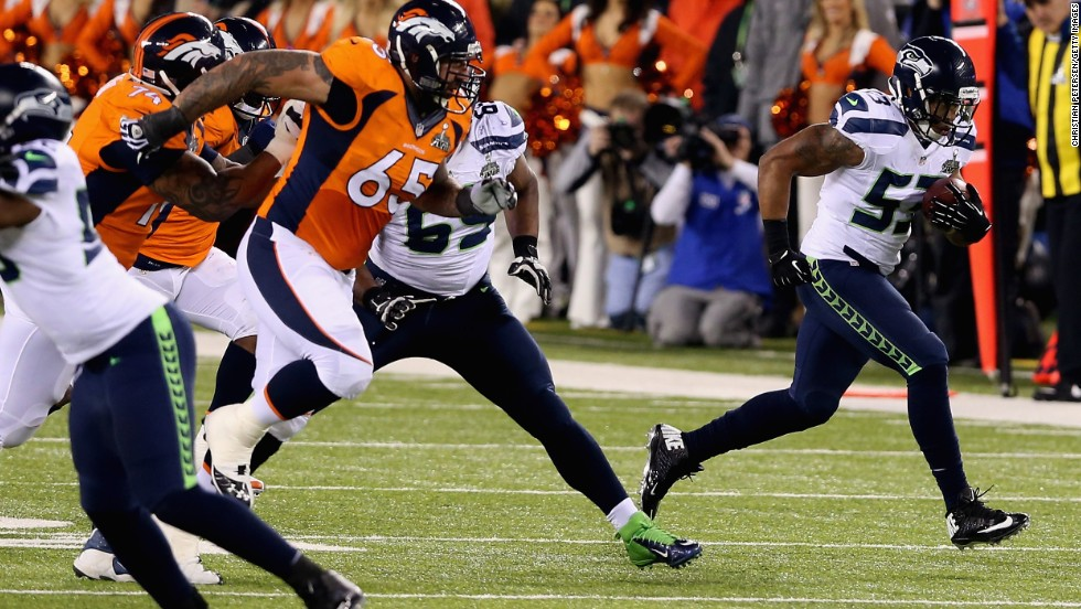 Smith has intercepted Manning's misplaced pass and is charging towards the end zone to score a touchdown.