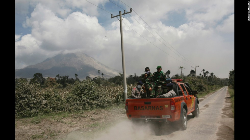 Indonesian soldiers ride in a truck in Payung village on February 3 to search for victims of the eruption.