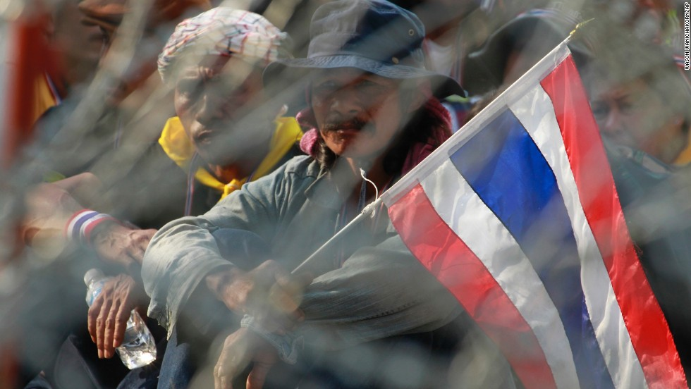 Protesters stake out positions behind barbed wire during a rally in Bangkok on February 3.