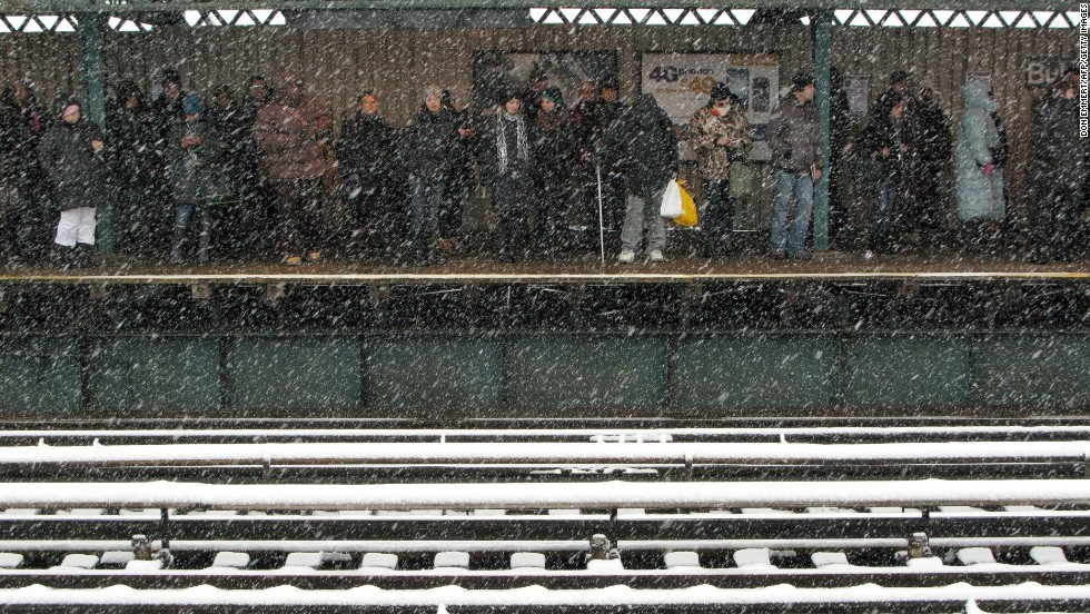 Commuters wait for a train as snow falls in New York on February 3.