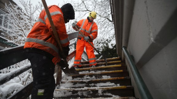 City workers clear snow and ice from stairs in Brooklyn on February 3.