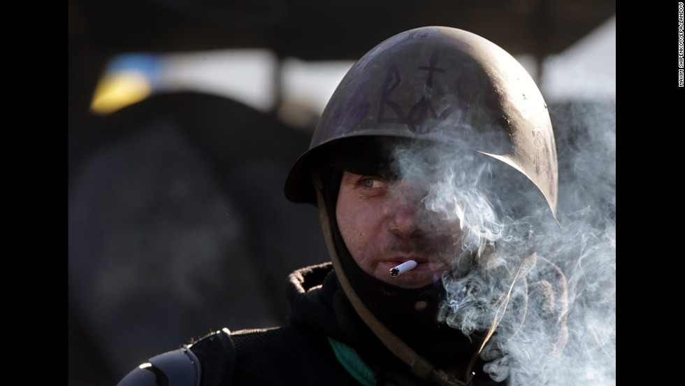 A protester smokes a cigarette while standing guard in Kiev on February 4.