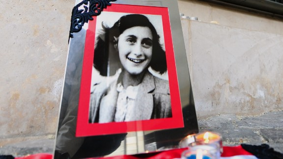 A portrait of Anne Frank stands in front of the memorial of Central Europe