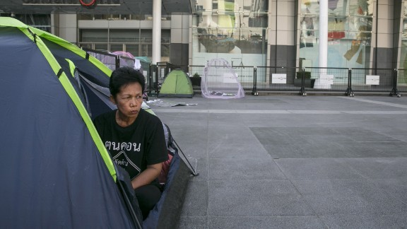 """BANGKOK, THAILAND - FEBRUARY 4: An anti-government protestor camps out in front of the Central World shopping mall at one of the protest sites in the shopping district February 4, 2014 in Bangkok, Thailand. Business has reportedly suffered and hotels are dealing with major losses as the political turmoil continues without any end in sight. The recent controversial elections exposed an increasingly bitter divide in the country. After disrupting the general election, anti-government demonstrators are continuing their campaign to oust Prime Minister Yingluck Shinawatra and the three week old """"Bangkok Shutdown, """" has blocked major intersections. The Thai government imposed a 60-day state of emergency in Bangkok and the surrounding provinces in an attempt to cope with the on-going political turmoil however this decree has had no effect on the mass protests. (Photo by Paula Bronstein/Getty Images)"""