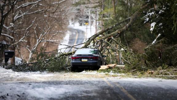 A tree limb fallen across a utility line and an abandoned car block a road in Media, Pennsylvania, on Thursday, February 6.