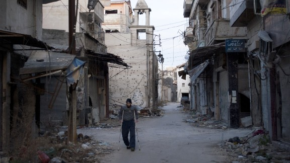 A man uses crutches as he walks past damaged buildings in a neighbourhood, besieged by government forces, in the central Syrian city of Homs on February 1, 2014.