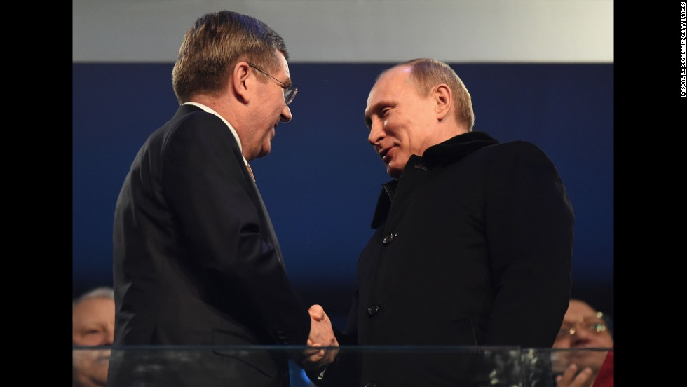 Thomas Bach, president of the International Olympic Committee, shakes hands with Russian President Vladimir Putin, right.