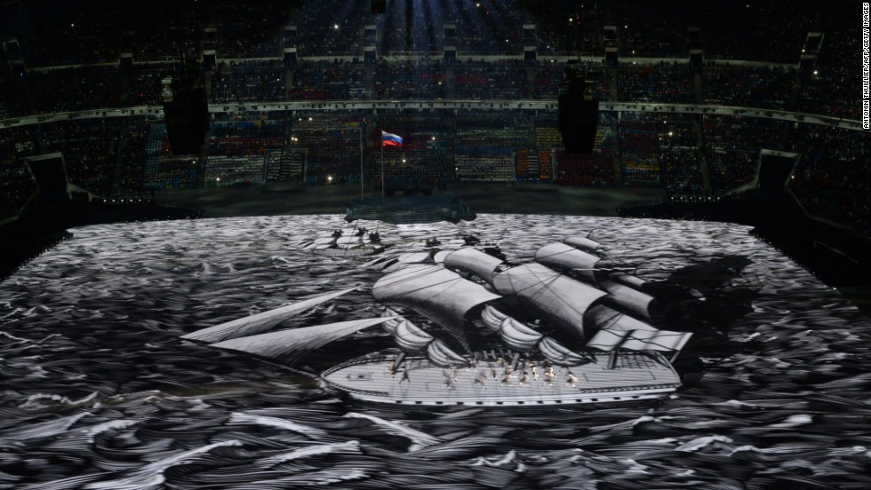 People move as a boat is projected across the floor of the stadium.