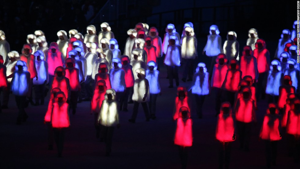 Performers in illuminated red, white and blue outfits prepare to form the Russian national flag.