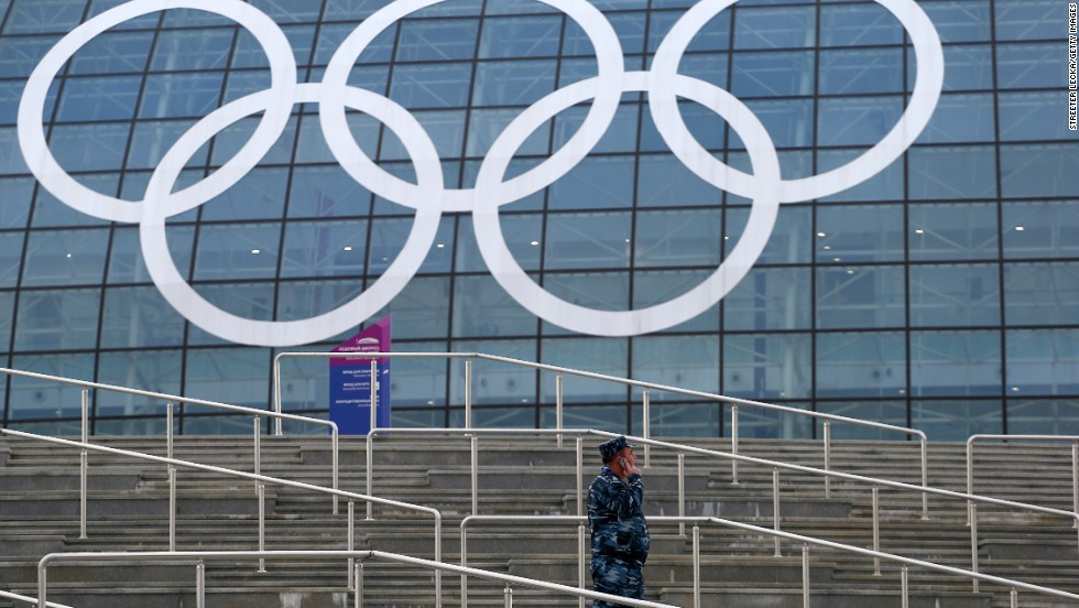 A security guard talks on a phone in front of the Bolshoy Ice Dome at the Olympic Park in Sochi on Tuesday, February 4.