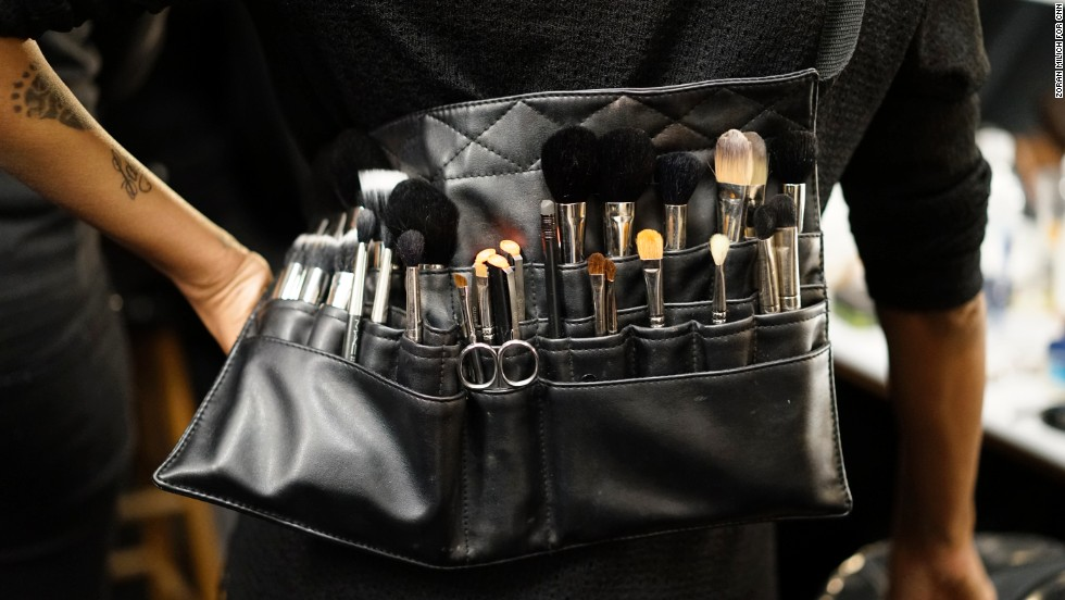 A makeup artist wears a brush apron belt for easy application.