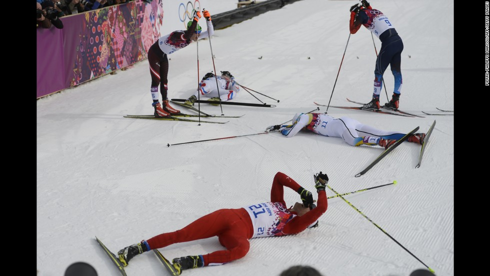 Swiss skier Dario Cologna, foreground, lies on the snow alongside other competitors in the men's skiathlon.