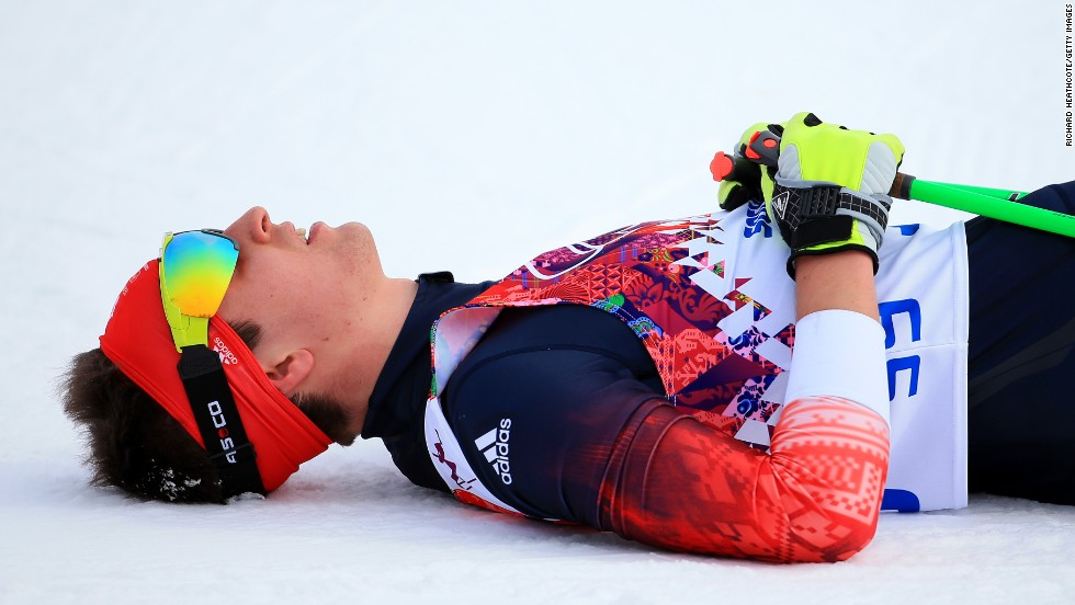Callum Smith of Great Britain rests at the finish line of the men's skiathlon.