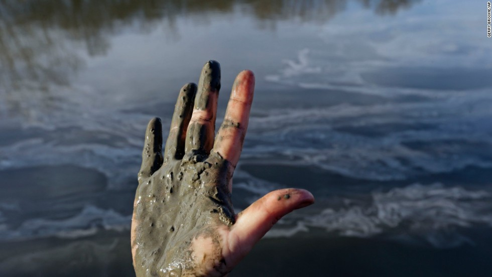 Amy Adams, North Carolina campaign coordinator with Appalachian Voices, shows her hand covered with wet coal ash from the Dan River on February 5.