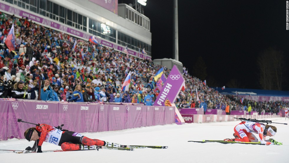 Canada's Megan Heinicke, left, and Poland's Monika Hojnisz collapse in the snow after competing in the 7.5-kilometer biathlon sprint on February 9.
