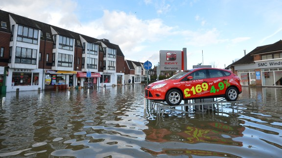 A car dealership's display model sits on a ramp above floodwaters in Datchet, England, on Monday, February 10. Britain has been hit by bad weather since early December, and swaths of southwestern England have been flooded in continuously stormy weather.