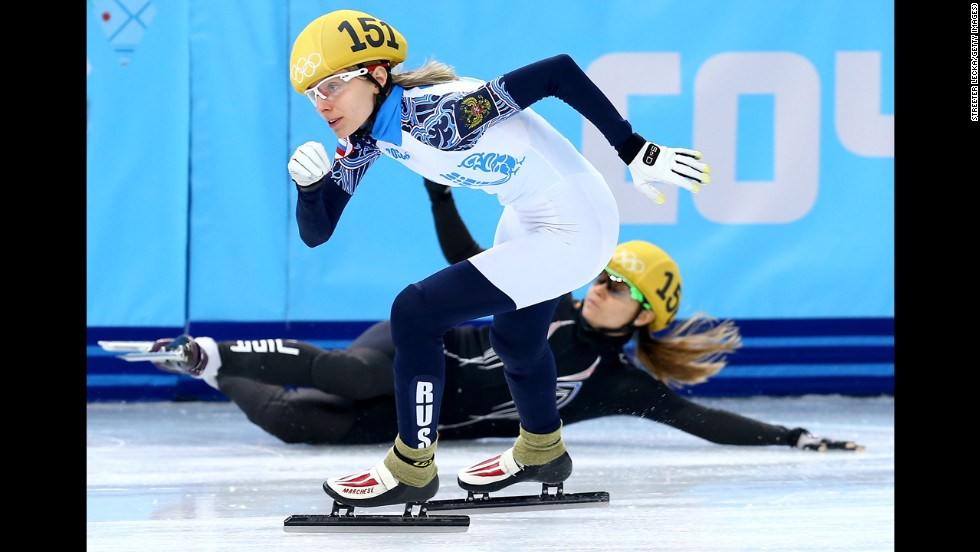 Short track speedskater Jessica Smith of the United States falls as Valeriya Reznik of Russia skates past her during the 500-meter preliminaries on February 10.