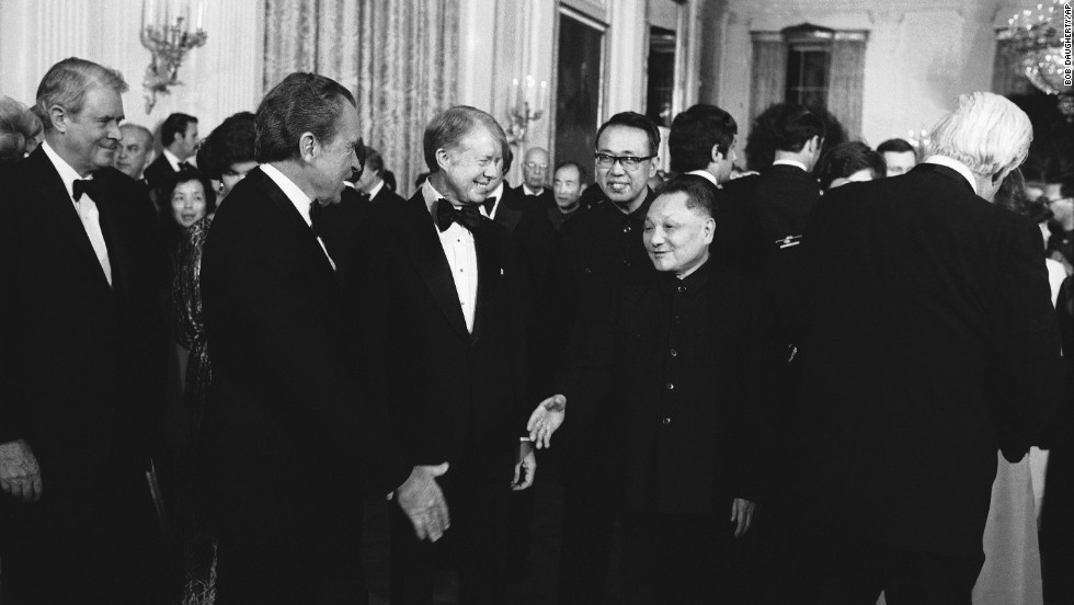 Former President Richard Nixon shakes hands with Chinese Vice Premier Teng Hsiao-ping as then-President Jimmy Carter looks on at a state dinner on January 29, 1979.