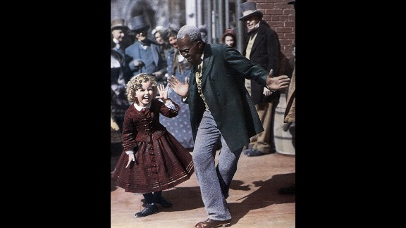 """Billy """"Bojangles"""" Robinson and Shirley Temple dance together on set in 1935."""