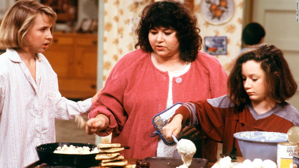 "Roseanne Barr as Roseanne Conner, who worked in a plastics factory, and later owned a restaurant, in ""Roseanne."""
