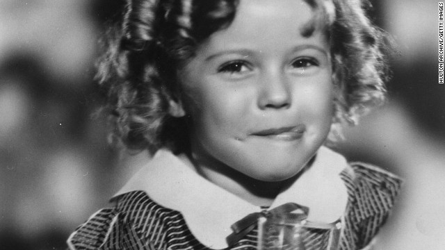 Shirley Temple (1928 - ) the American child star started performing in films at three years. She entered politics in the 60's and took on several ambassador positions representing her country. Pictured enjoying a soft drink with an impish grin on her face. (Photo by Hulton Archive/Getty Images)