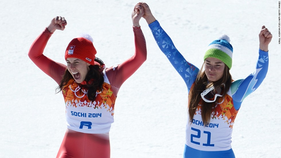 Dominique Gisin of Switzerland, left, and Tina Maze of Slovenia stand on the podium together after tying for the gold medal in the women's downhill February 12. The two skiers both finished their run with a time of 1:41.57.