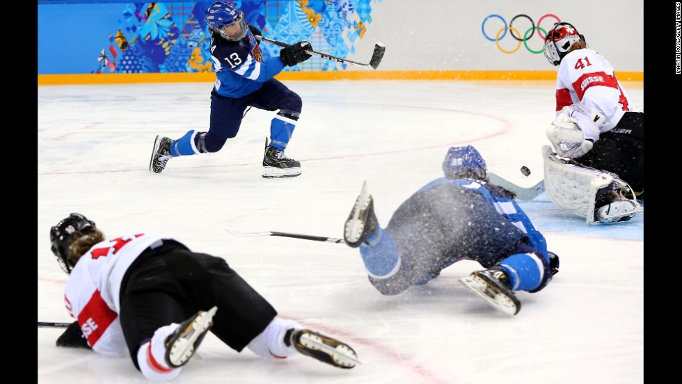 Riikka Valila of Finland takes a shot against Florence Schelling of Switzerland while teammates crash on the ice during a women's hockey game February 12.