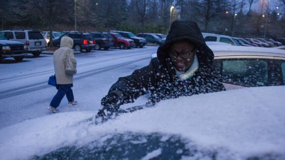 Shmetrice Moore, a nurse at an Emory University hospital in Johns Creek, Georgia, scrapes snow and ice off her windshield as she and others are released early from their shift on February 12.