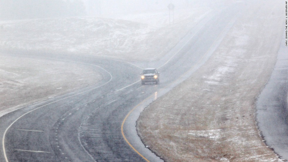 A vehicle drives through falling snow on the U.S. 421 bypass in Sanford, North Carolina, on February 11.