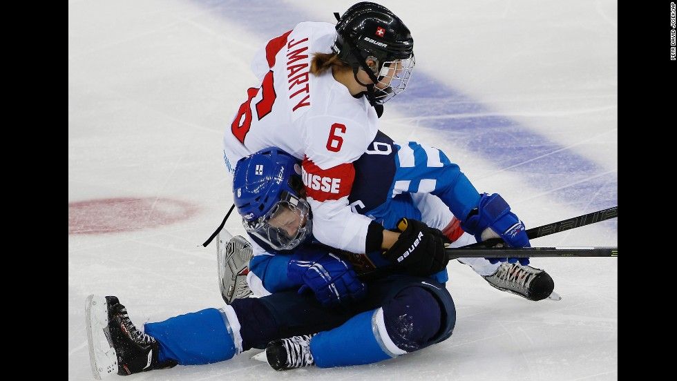 Julia Marty of Switzerland and Jenni Hiirikoski of Finland collide during the second period of their women's hockey game February 12.
