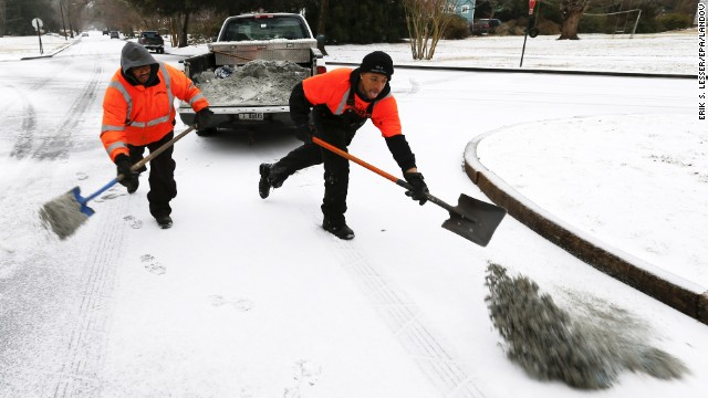 City public works employees spread a mixture of sand and salt on an intersection in Avondale Estates, Georgia, on Wednesday, February 12.