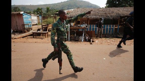 A Central African Republic police officer chases looters attacking a broken-down truck Friday, February 7, in the capital of Bangui. The country, a former French colony, was plunged into chaos last year after a coalition of mostly Muslim rebels ousted President Francois Bozize.