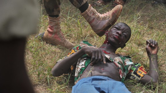 A Central African Armed Forces member kicks the man suspected of being a former Seleka rebel.