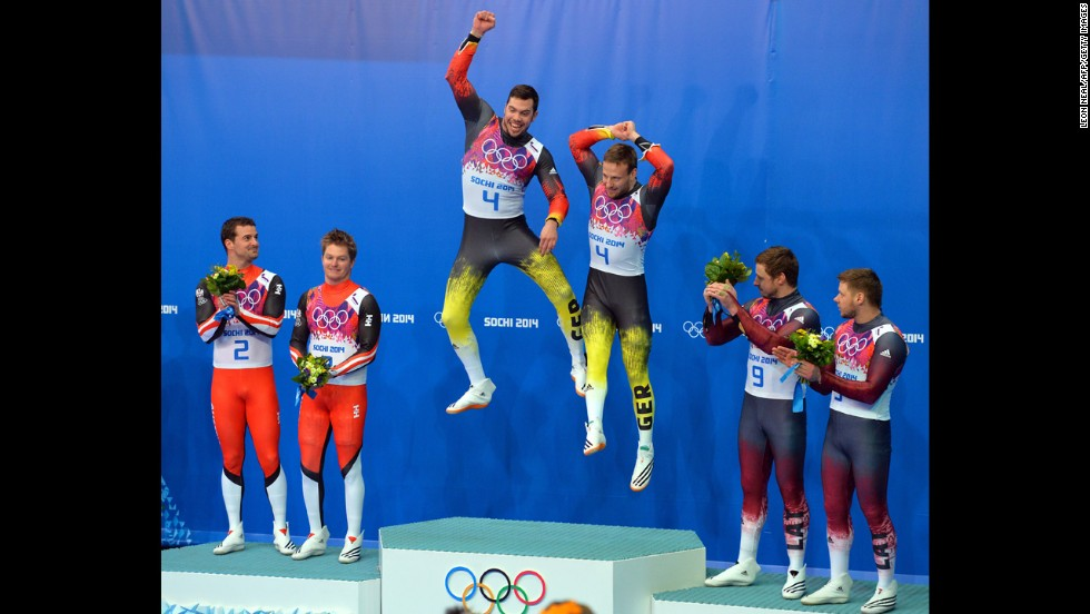 Germany's Tobias Arlt and Tobias Wendl jump on the podium after winning gold in luge doubles on February 12.