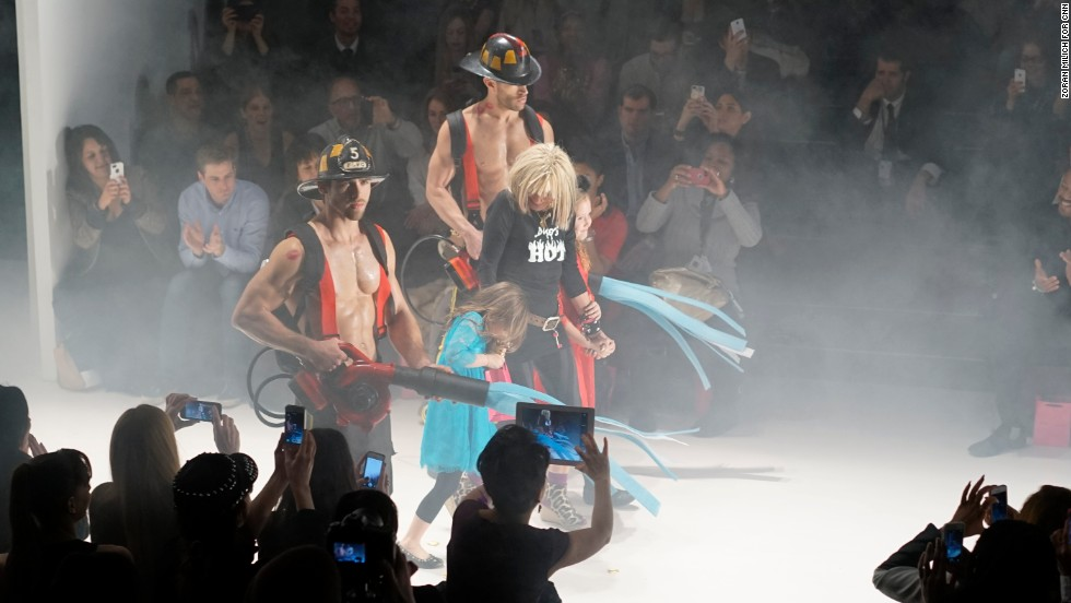 "Betsey Johnson, who is 71 years old, showed her ""Betsey's Hot"" collection on February 12. Fittingly, she came out with firefighters (and her granddaughters!) at the end of the show."