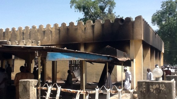 People walk around the damaged mosque in the village of Konduga, after an attack in February 2014.