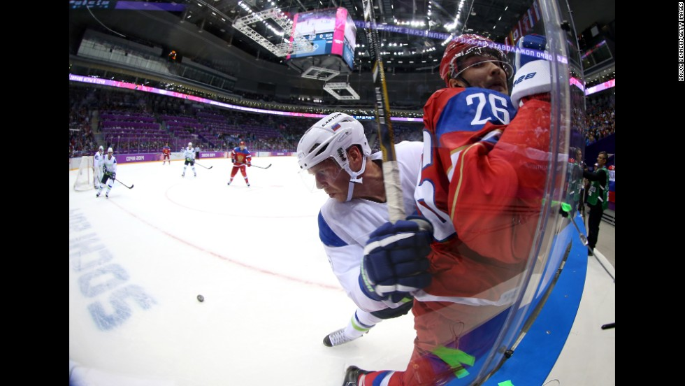 Andrej Tavzelj of Slovenia checks Vyacheslav Voynov of Russia into the glass during the men's hockey game on February 13.