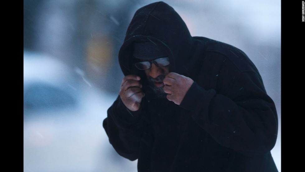 A man in Philadelphia shields his face from the elements February 13.