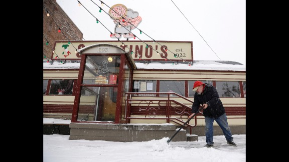 Lyall MacFee shovels snow in front of Sciortino's Pizzeria in Albany, New York, on February 13.