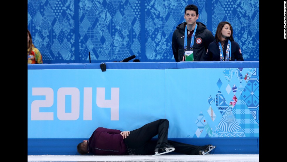 Jeremy Abbott of the United States hits the wall in front of his coaches, Yuka Sato and Jason Dungjen, while competing in the men's individual event on February 13.