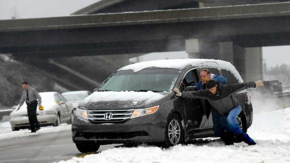 Motorists push a vehicle on Highway 70 in Raleigh, North Carolina, on February 13, a day after the worst of the storm struck the town.